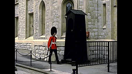 охранять : LONDON, UNITED KINGDOM - CIRCA 1977: guard of the Tower of London marching in red uniform. Archival of London city of England in the 1970s.
