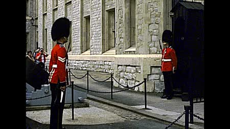 охранять : LONDON, UNITED KINGDOM - CIRCA 1977: Changing the Guard ceremony at the Tower of London. Buckingham Palace soldiers in red uniform. Archival of London city of England in the 1970s.