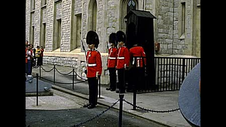 охранять : LONDON, UNITED KINGDOM - CIRCA 1977: Changing the Guard at the Tower of London castle. Buckingham Palace soldiers and officer in red uniform. Archival of London city of England in the 1970s.