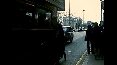 dubbeldekker : LONDON, UNITED KINGDOM - CIRCA 1977: people catching red double-decker bus and Taxicab, Austin FX4. Archival of London in 1970s. Stockvideo