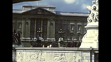 autobus : LONDON, UNITED KINGDOM - CIRCA 1977: Royal Standard flag on top of Buckingham Palace, official flag of the reigning British sovereign and the only flag to fly until 1997. Royals guards in red uniform.
