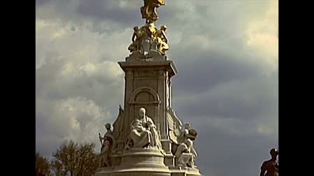 buckingham palace : LONDON, UNITED KINGDOM - CIRCA 1977: monument to Queen Victoria: Victoria Memorial golden statue at Buckingham Palace with tourists. Archival of London city of England in the 1970s. Stock Footage