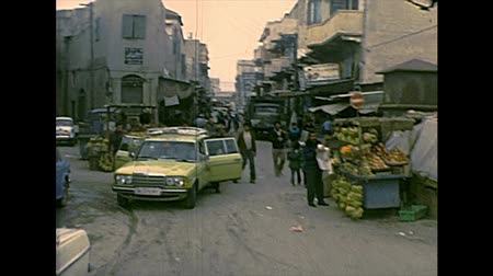 palestina : GAZA, PALESTINE, ISRAEL - 1979: Streets life of the old town with local people in typical Palestinian dress, working and shopping in the markets and fruit stalls. Archival of Israel Palestine in 1970s Stock Footage