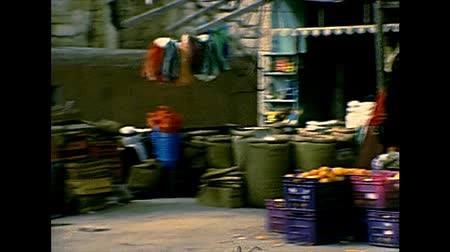 yahudi : BETHLEHEM, WEST BANK, ISRAEL- CIRCA 1979: street seller of clothes in the old local market of the town. Historic archival footage of Israel and Palestine in the 1970s. Stok Video