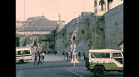 church of the nativity : BETHLEHEM, WEST BANK, ISRAEL- CIRCA 1979: Church of the Nativity with tourists in pilgrimage and UN cars. Historic archival footage of Israel and Palestine in the 1970s. Stock Footage