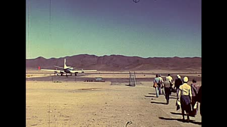 bibliai : SINAI, EGYPT - circa 1979: tourists on tour catching a flight in a small airport in Sinai Peninsula, visiting Saint Catherine Christian Monastery. Archival Mount Sinai of Egypt in 1970s. Stock mozgókép