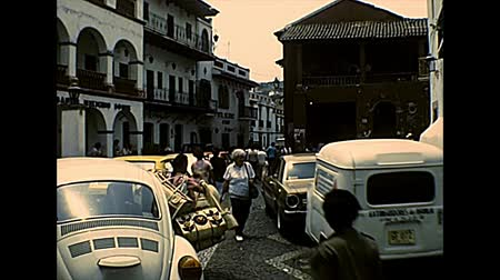 super car : TAXCO DE ALARCON, MEXICO - circa 1970: Taxco downtown narrow roads, buildings, and restaurants. Typical Volkswagen Beetles cars. Archival of Mexico in South America in the 1970s. Stock Footage