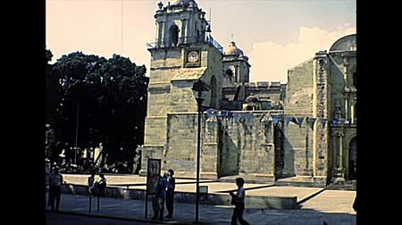 семидесятые годы : OAXACA DE JUAREZ, MEXICO - circa 1970: clock tower on the right side of the Cathedral of Our Lady of the Assumption in the city of Oaxaca. Archival of Mexico in Oaxaca state in the 1970s. Стоковые видеозаписи