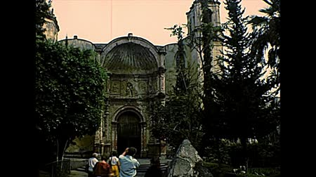 colonial : CUERNAVACA, MEXICO - circa 1970: tourists visiting the Mexican Catedral de Cuernavaca. Entrance gate and garden. Archival of Mexico in Morelos state, South America in 1970s.