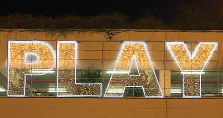 csillogás : Christmas lights with PLAY text background with golden Christmas lights in yellow and orange colors.