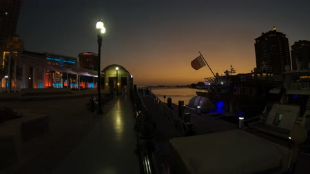 Doha, Qatar - February 18, 2019: amazing sunset in marina walkway promenade in Porto Arabia, the Pearl, with the Yasmine Palace restaurant on background. Persian Gulf in Middle East.