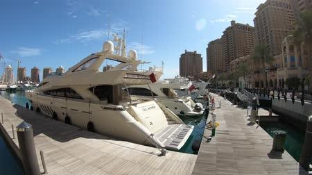 docked : Doha, Qatar - February 18, 2019: luxurious yachts and boats docked at Porto Arabia Marina. The Pearl-Qatar in Doha artificial island and a popular tourist destination in Persian Gulf, Middle East.