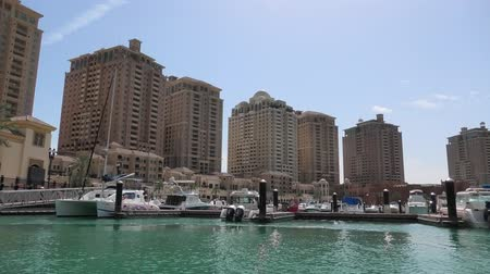 porto arabia : Doha, Qatar - February 18, 2019: sea view of marina waterfront, popular attraction of Porto Arabia, the Pearl residential buildings. Persian Gulf in Middle East. Sunny day, blue sky. Stock Footage
