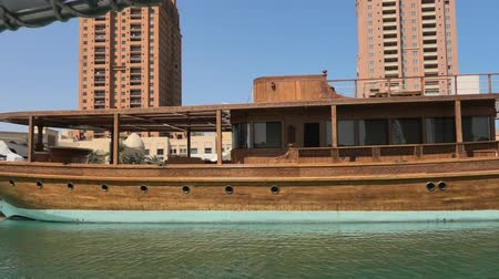porto arabia : Doha, Qatar - February 18, 2019: traditional wooden boat docked in Porto Arabia at the Pearl-Qatar with residential buildings on background. Persian Gulf in Middle East. Sunny blue sky. Stock Footage