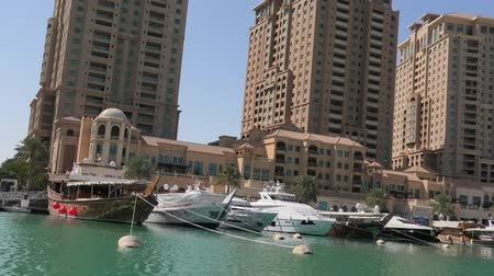 porto arabia : Doha, Qatar - February 18, 2019: Marina corniche promenade with luxury boats and yachts in Porto Arabia at the Pearl-Qatar. Residential towers on background. Persian Gulf, Middle East. Sunny blue sky.