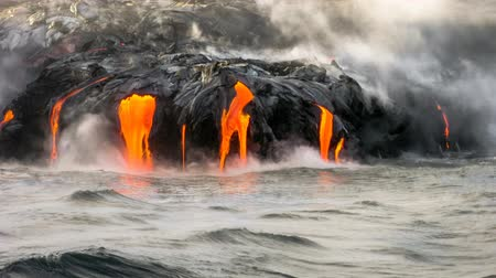 курение : Sea view of Kilauea Volcano in Big Island, Hawaii, United States. A restless volcano that has been in business since 1983. Cinemagraph loop with lava flowing in the dark and jumping into the sea.