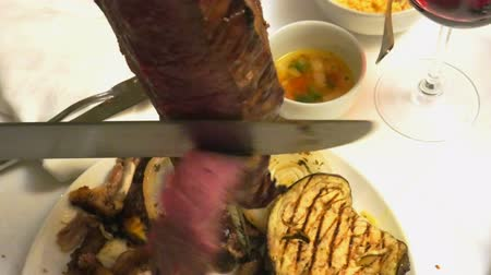 plivat : Close up of a picanha roast beef cut on the sword in Brazilian churrasqueira: typical Brazilian restaurant with grill.