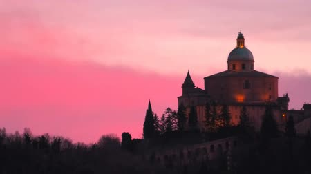 madona : Distant view of Sanctuary of Blessed Virgin of San Luca on Colle della Guardia in Bologna. Twilight in the winter, pink sky with Copy space. Historical church and pilgrimage destination in Italy. Dostupné videozáznamy