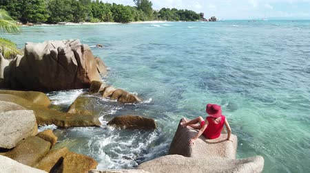 sunhat : SLOW MOTION: Happy tourist woman in red dress looking Anse Severe Beach from granite blouder stones. La Digue, Seychelles, Indian Ocean. Female lifestyle enjoying summer holidays at tropics. Stock Footage