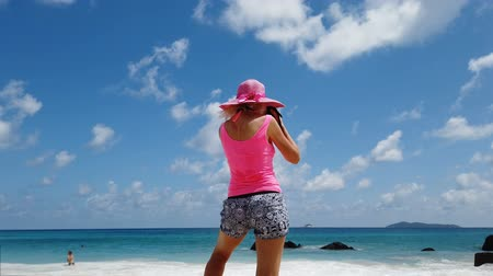 sunhat : woman photographer with hat on a large granite boulder in popular and scenic Anse Lazio beach. Female lifestyle by turquoise waters of Indian ocean on Praslin Island, Seychelles. Summer holidays. Stock Footage