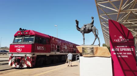 legendary : Alice Springs, Northern Territory, Australia - Aug 29, 2019: carriages of famous Ghan railway at a morning stop in Alice Springs Train Station and The Ghan Memorial: statue of Afghan worker and camel.