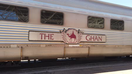 mozdony : Alice Springs, Northern Territory, Australia - Aug 29, 2019: famous Ghan railway at a morning stop in Alice Springs Train Station and The Ghan Memorial: statue of Afghan worker and camel. Stock mozgókép