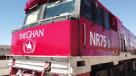 legendary : Alice Springs, Northern Territory, Australia - Aug 29, 2019: perspective red historic The Ghan luxury passenger train locomotive stopped at Alice Springs station on Adelaide-Darwin route in sunny day.