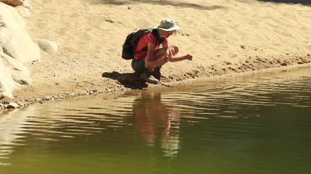 west macdonnell national park : Backpacker woman resting on lake of Ormiston Pound Walk, a circuit that follows the rocky slope of pound and back along the gorge by main waterhole.West MacDonnell Range, Australia, Northern Territory
