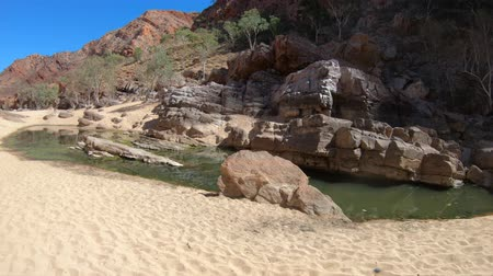 west macdonnell national park : Rugged rocky cliffs of Ormiston Gorge in West MacDonnell Range National Park reflected in a pool on the river in dry season. Northern Territory, Central Australia, Outback Red Centre. Stock Footage