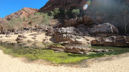 západ : rugged rocky cliffs of Ormiston Gorge in West MacDonnell Range National Park reflected in a pool on the river in dry season. Northern Territory, Central Australia, Outback Red Centre. Dostupné videozáznamy
