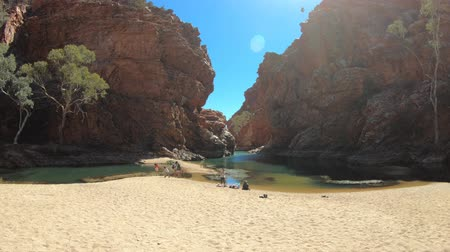 rugók : Northern Territory, Australia - Aug 18, 2019:Tourists sunbathing on golden sand of Ellery Creek Big Hole at popular waterhole in a gorge surrounded by red cliffs in West MacDonnell Ranges.
