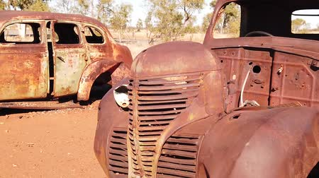 zkorodované : SLOW MOTION: Sunbeams of sunset on rusty wrecks of old cars. Australia, Northern Territory in Red Centre desert. Dostupné videozáznamy
