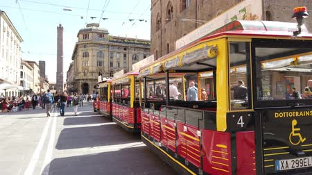 oszlopok : Bologna, Italy - September 21, 2019: historical red train in via Rizzoli by Piazza Maggiore square. Tour of historic downtown of Bologna city.