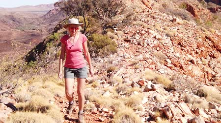 west macdonnell national park : Carefree woman hiking in SLOW MOTION by Mount Sonder, one highest mountains in Northern Territory, Australia Outback. Vastness of Ormiston Gorge, hiking Ormiston Pound Walk in West MacDonnell Ranges.