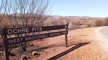 sacred site : signboard of Ochre Pits a minerals rock formation ochre on dry creek in West McDonnell Ranges. Popular destination in Northern Territory, Australia. Ochre is used by Aborigine people for ceremonies Stock Footage