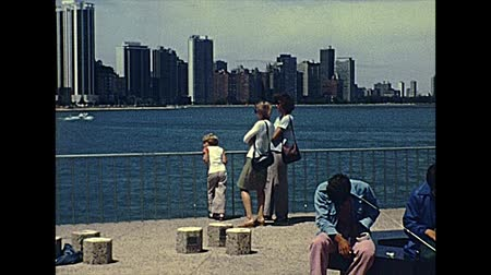 ミシガン州 : Chicago, Lake Michigan, Illinois, United States - Circa 1977:people resting and fishing by the waterfront skyline of Ohio Street Beach. Vintage dress of 70s people. Historical United States of America
