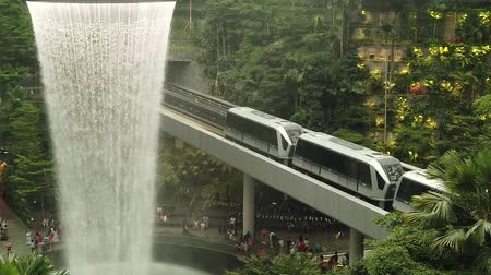 asma : Singapore - Aug 8, 2019: railway bridge with skytrain transporting tourists in Changi International Airport. Rain Vortex, indoor waterfall of Jewel Airport. SLOW MOTION