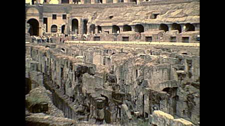 археологический : ROME, ITALY - circa 1986: Rome coliseum interior with tourists visiting, Flavian Amphitheatre, largest amphitheater in the world of Rome city. Historical archival of Rome capital of Italy in 1980s. Стоковые видеозаписи