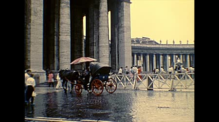 cavalo vapor : VATICAN CITY, ROME, ITALY - 1986: horse-drawn carriage with tourists and old yellow taxi in Saint Peter square of Rome in Italy with Saint Peter church. Archival of Rome capital of Italy in the 1980s.