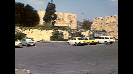 典型的な : ACRE, ISRAEL - CIRCA 1979: Old Acre town roads and walls with local people in typical traditional Islamic dress and with vintage cars. Archival footage in the 1970s of Israel.