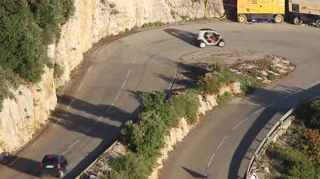 two seater : La Turbie, France - November 4, 2015: Electric City Cars (White and Black Renault Twizy Smart Fortwo) was Steep Mountain Road Turn in the French Alps