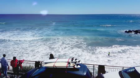 many surfers : San Remo, Italy - May 2, 2017: Car With Surfboards On The Roof. Surfers On The Waves In The Background. San Remo Beach, Italy - 4K Video
