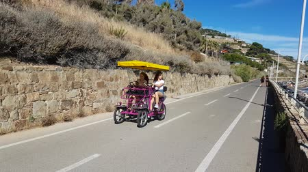 two wheeled : San Remo, Italy - August 13, 2017: Two Teen Girls Riding Quadracycle on Cycle Path in San Remo, Liguria, Italy