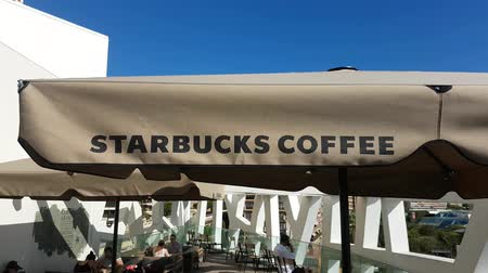 franczyza : Monte-Carlo, Monte-Carlo, Monaco - September 5, 2017: Starbucks Coffee In The Background, Customers of Starbucks Drinking Coffee Outside of the Terrace in Monte Carlo, French Riviera - 4K Video
