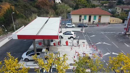 pompki : Menton, France - December 16, 2017: Aerial View of an Intermarket Gas Station (Petrol, Diesel) in Menton on the French Riviera. Intermarchà © is the Brand of a General Commercial French Supermarket - 4K Video Wideo