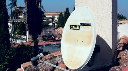 old radio : Granada, Spain - April 3, 2017: Canal Satelite Digital. White Satellite Dish On The Roof House. Satellite Dish Hanging on the Chimney House
