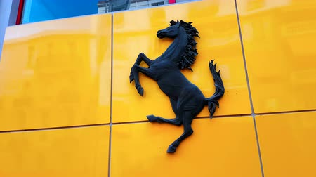 хром : Monte-Carlo, Monaco - February 18, 2018: Ferrari Black Horse Prancing And Ferrari Text Logo on the Wall of a Shop. The Prancing Horse is The Symbol of Italian Sports Car Manufacturer Ferrari And Its Scuderia Ferrari Racing Division - 4K Video Стоковые видеозаписи