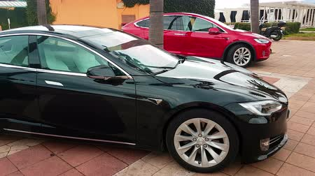 por que : Menton, France - March 3, 2018: - Luxury Black Tesla Model S And Red Tesla X Model Electric Cars Parked on a Square in Menton on The French Riviera - 4K Video Stock Footage