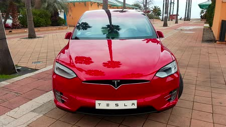 tesla motors : Menton, France - March 3, 2018: Red Tesla X Model Electric Car Parked on a Square in Menton on The French Riviera. Tesla Model X is a Luxury Full-Sized SUV, All-Electric Crossover - 4K Video