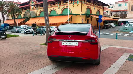 tesla motors : Menton, France - March 3, 2018: Red Tesla X Model (Rear View) Electric Car Park on a Square in Menton on The French Riviera. Tesla Model X is a Luxury Full-Sized SUV, All-Electric Crossover - 4K Video